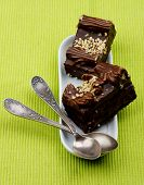 foto of chocolate spoon  - Chocolate Mocha Cakes Mocha Frosting Cream and Nuts on White Dessert Plate with Silver Tea Spoons closeup on Green Textile background - JPG