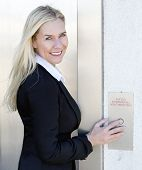 stock photo of elevators  - blond woman in business attire standing by the elevator - JPG