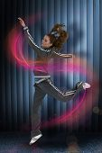 stock photo of dark side  - Full length side view of a sporty young blond jumping against dark grey room - JPG