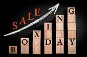 foto of boxing day  - Message BOXING DAY SALE on ascending arrow above bar graph of Wooden small cubes isolated on black background - JPG