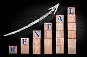 picture of ascending  - Word RENTAL on ascending arrow above bar graph of Wooden small cubes isolated on black background - JPG