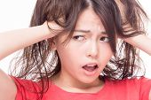 image of pulling hair  - Frustrated and stressed angry Chinese woman pulling her hair with hands - JPG