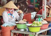 image of stall  - Traditional asian market stall with traditional dishes and seller in conical hat - JPG