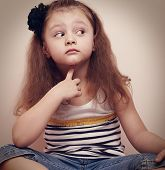 image of pry  - Thinking prying kid girl sitting in jeans with finger under face - JPG