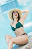 pic of sunbather  - Pretty young woman sunbathing by the pool - JPG