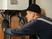 picture of pipefitter  - Man connects the gas boiler to the pipes with a wrench - JPG