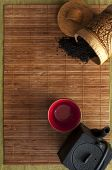 image of black tea  - on bamboo Mat cast iron kettle and a Cup of hot tea spilled black tea