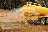 image of tank truck  - A water truck sprays water on a fresh fill layer of soil and rock for a new road construciton project - JPG