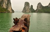 foto of dragon head  - A wooden dragon head bow protuding from a boat with the islands of ha long bay vietnam in the background.