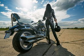 foto of biker  - Biker girl in leather jacket standing by a motorcycle - JPG