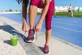 Healthy lifestyle woman runner tying running shoes drinking green smoothie cup juice drink before ra poster