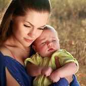 attractive young mother and little baby boy outdoors