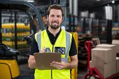Smiling factory worker writing on clipboard in factory poster