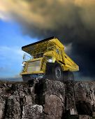 stock photo of jcb  - Heavy duty construction vehicle on rocky hill against stormy looking sky - JPG