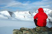 Постер, плакат: Альпинист сидя на камне глядя на большой ледник заснеженные горы Западная Альпы Италия