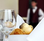 table setting in restaurant with bread empty glass and waiter off focus
