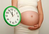 Pregnant woman with a clock waiting anxiously for the birth of her baby. Nine month. Third trimester. poster