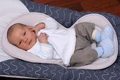 Newborn baby laying in bouncer chair. Two weeks old baby