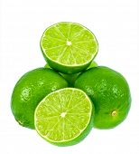 Green limes isolated on a white background. One lime is cut in half.