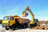 Excavator loading dump truck tipper at open cast over blue sky in winter