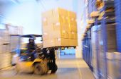 Electric forklift in warehouse loading cardboard boxes. Intentional optical zooming blur