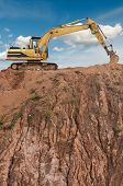 loader excavator in open sand mine over scenic blue sky