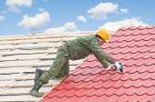 worker on roof at screwdriving works with metal tile and roofing iron