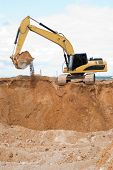 Yellow excavator loader at construction site with raised bucket full of sand