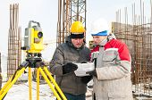 Discussing Surveyor worker and assistant at construction site in winter with theodolite equipment