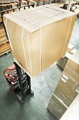warehouse stacker forklift lifting large cardboard box