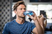 Young man drinking water after sports. Portrait of handsome muscular man drinking a bottle of water  poster