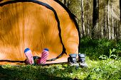 Shoes off mountaineer sleeping inside tent
