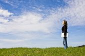 picture of coy  - Young woman with laptop in meadow - JPG