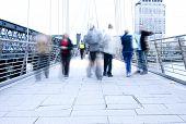 Blurred people walking over the bridge.