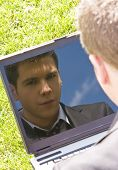 Young businessman reflected in his own computer.