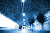 Blurred people on tunnel, blue toned.