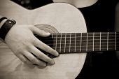 Hand on guitar, old sepia toned.