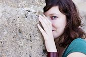 Young smiling woman observing behind wall