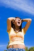Screaming woman over blue sky as background.