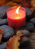 Spa Candle with flat river rocks over bamboo