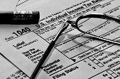 Zeit, den Steuern zahlen, eine schwarze und weiße Brille, Bleistift und uns 1040 Steuerformular.