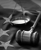 Law and Justice - black and white image of a gavel, scale and US flag background.