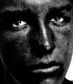 Eyes Of Need - a young person with a dirty face looks for help. Black and white.