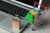 Buying Goods And Clothing In The Online Store. Shopping Bags In Shopping Cart On Laptop Keyboard. poster