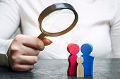 A Woman Is Holding A Magnifying Glass Over The Wooden Figures. Studying Family Composition, Needs An poster