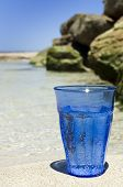 a Blue drinking glass with sparkling water on the beach.