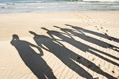 stock photo of crew cut  - The silhouettes of five people on the beach - JPG