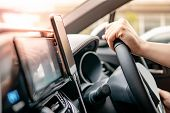 Male Driver Hand Holding On Steering Wheel Using Smartphone For Gps Navigation. Mobile Phone Mountin poster