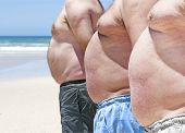 stock photo of beer-belly  - Close up of three obese fat men on the beach showing their unhealthy bellies - JPG