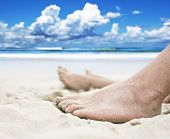 Feet of a man and woman lying on the beach